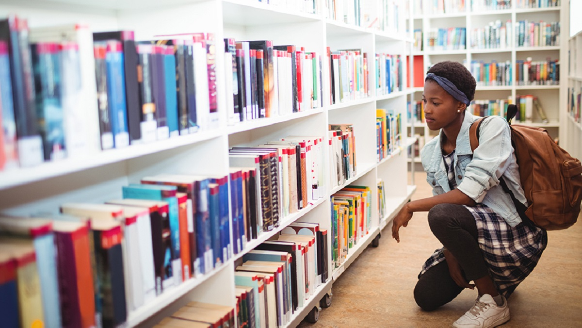Student kneeling in front of a shelf of books thinking