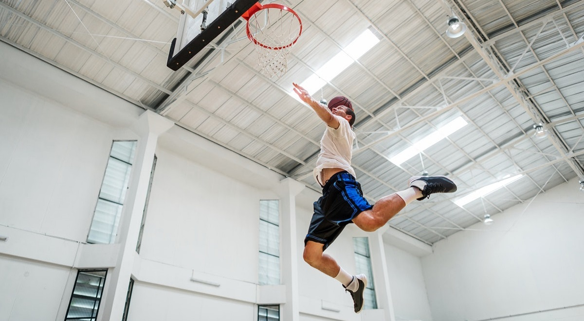 Student leaping to make a basket
